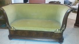 Early 1800's French Empire flame mahogany settee with gilt details.