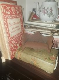 Cookbooks, the green one is very old. Moss rose teapot. There is also a childs set. Little wrought iron couch, nice pantina.