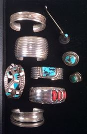 Navajo sterling jewelry - top to bottom: Signed Cheyenne Harris bracelet, candle snuffer with turquoise stone on top, signed wide cuff with channels by Darrell Slim, Zuni Kachina bracelet, signed Orville Tsinnie bracelet with dots, channels & turquoise, unmarked turquoise ring (NOTE: lower ring is not available - owner decided to keep it), signed Dan Jackson bracelet with coral, unidentified sterling bracelet with slit