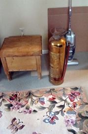 Antique wood toilet and copper fire extinguisher.
