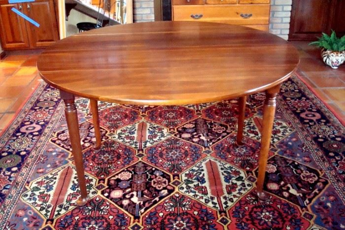 Solid cherry drop leaf table with two leaves and pads.