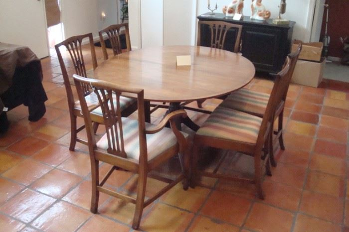 Elegant Baker Vintage Duncan Phyfe style dining table with three leaves, and set of six Biggs Hepplewhite style mahogany chairs.