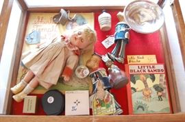 Showcase at check out table is full of treasures, Tin Wind Up Toy Popeye, Original Shirley Temple w clothes and booklet, 2 different advertising Cocal Cola openers ( 1 I have never seen), Little Black Sambo 1937, Sterling, Advertising Whiskey Jug
