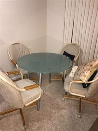 GLASS ROUND TABLE AND 4 ROLLING CHAIRS