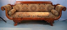 024a  Mahogany Empire sofa with heavily carved legs, scroll arms and green upholstery, 35 in. T, 7 ft. 3 in. T, 20 in. D.