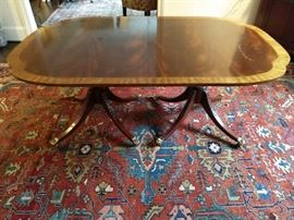 """Extremely high end Baker Historic Charleston Collection Mahogany Dining Table in the Duncan Phyfe Style featuring a table top with wide satinwood band and scalloped shaped edges sitting on top of two intricately carved acanthus leaves on the urn shaped bases with four saber legs that curve outward terminating in brass paw feet on casters. Table comes with 2 leaves.                                                              Measurements: 29"""" H X 46"""" D x 70"""" W unopened. Each leaf is 16.5"""". Table opens to 103""""."""