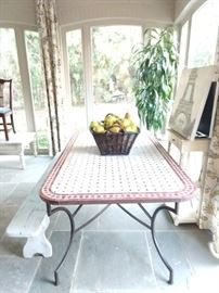 Bring artistic color to your  décor with this  rectangular metal outdoor bistro patio table with hand-laid red and white tiles. Made with legs of durable tubular steel, it boasts a top of hand-laid tiles. Its artful design is complemented by a black powder coat finish that keeps it looking good all season long. Keeping it clean is easy too, just hose it down and let the warmth of the sun dry it off. Enjoy a morning cup of your favorite brew or a glass of wine with a friend on this delightful table.  Basket of French pears perfectly compliments the mood!