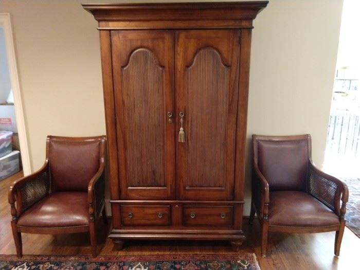 "Stately wooden armoire, flanked by a pair of leather/cane armchairs, by ""Our House Designs""."