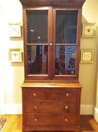 Primitive American pine cabinet, with wavy glass doors and three drawers.