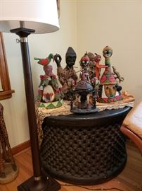 """Unique African side table - drum shaped form with chain-like pattern surrounding - 24""""H x 32"""" diameter; floor lamp - 56""""H;  African crowns, wood with beading, Yoruba types from Nigeria - 21"""" tall; African statues, carved wood with hemp and grass decoration."""