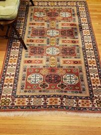 "Wool area rug 72"" x 48"".  Assorted geometrics in shades of cream, mustard, cinnabar, red and blue."