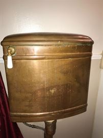 Antique wall-mount copper toilet tank with porcelain handle.