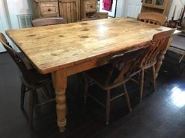 Large antique English country pine dining table with mismatched chairs.