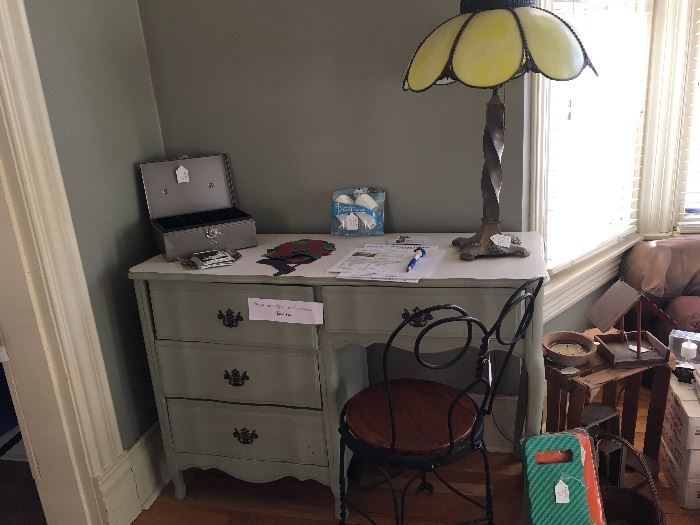 Nice desk with vintage sitting chair stained-glass lamp and a cashbox some small crates and kneeling pads