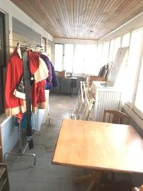 sleeping porch- sewing machine. clothes, small table with four chairs, wiker dresser