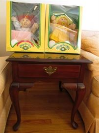 End table with Queen Ann style legs and a drawer.  Cabbage Patch Dolls are from 1982 and 1985. New in Box