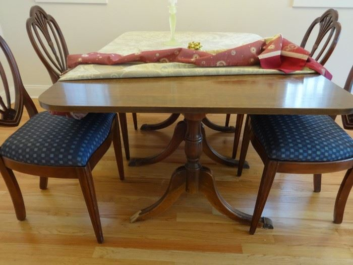 """Dark wood dining room table, the side ends fold down.  One 10"""" leaf is included. Size of table is 5' 6"""" long x 3'4"""" wide x 2'6"""" tall. One of the brass """"feet"""" end is missing."""