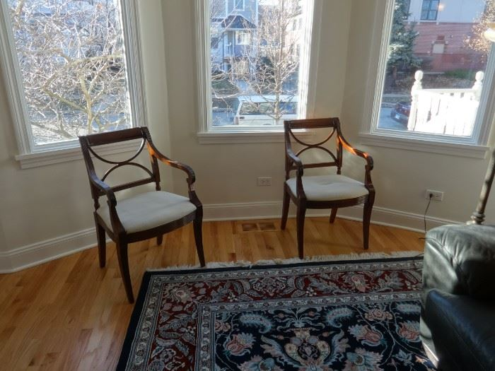 """Two living room side chairs, dark wood, and cream cushions. Could stand to be reupholstered. Size: 1'10"""" wide x 1'7"""" deep x 2'10"""" tall at the top. Pretty good condition."""