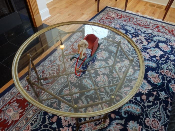 """Glass top coffee table bordered in brass, top lifts off of the brass base. Size: 3'2"""" diameter x 1'6"""" tall. Glass is heavy, base is not."""