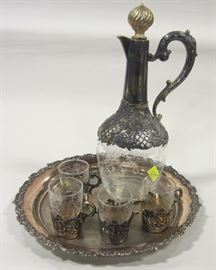 "Liquor decanter set made of 800 silver and etched glass. Has 8"" tray and four shot cups with glass inserts. Some gilding. Decanter is 8.5"" tall including the stopper. Weight of tray and cup bases 7.62 troy ounces"