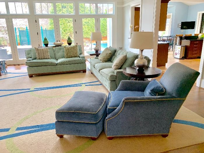 Great room sofas by TRS upholstered in ice blue basketweave and piped in brown leather.  One 86 inch sofa, one 74 inch sofa.  Club chair and ottoman upholstered in Sublime Ocean with contrasting welts in Putty.