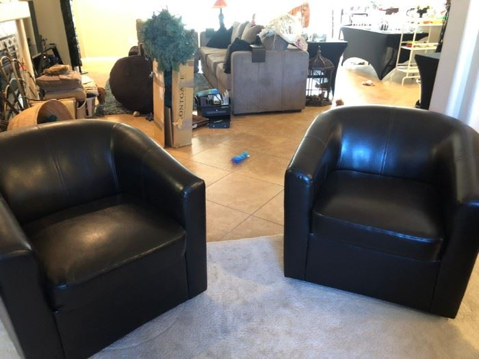pair of leather swivel barrel chairs