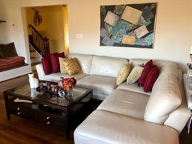Large leather sectional with dark wood and glass coffee table with storage.