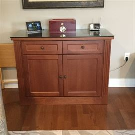 Handcrafted cabinet by local cabinet maker in Leland, NC. Ritenour Handcrafted Cabinet maker . Has a thick piece of glass covering the top surface.  Perfect for a bar cabinet. Will not go half off.