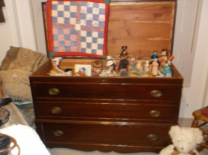 Mahogany cedar chest, doll collection, and handmade quilt