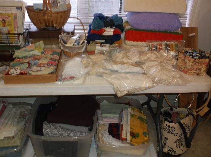 Sewing supplies, lace, fabric pieces, and yarn