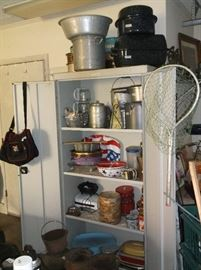 Two door metal cabinet and large cooking pots