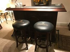 GUINNESS BAR AND PAIR OF BAR STOOLS IN DISTRESSED WALNUT.
