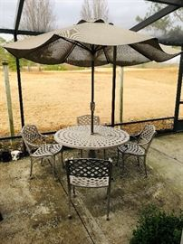 Wrought iron basket weave pattern patio set with umbrella.  Like new!Whether you're hoping to furnish a luxury outdoor lounge or patio dining layout, Windham's Meridian Collection has an option that's bound to please. The easy-to-coordinate style in this line are distinguished by crosshatched seats and backs, plus rolling arms that fit the body's natural contours. Crafted from cast aluminum of an exceptional quality, this understated furniture was designed to fit in just about anywhere, from a sophisticated cafe setting to your own backyard.All of their furniture is fully welded, requiring the touch of skilled workers who have completely mastered their craft. After the furniture is assembled, it's coated with chrome phosphate that provides reliable protection against saltwater and harsh weather conditions. Finally, trained artisans apply antique finishes to the furniture, giving the designs additional depth and individuality.