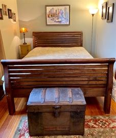 Queen sleigh bed and antique camel hump steamer trunk.