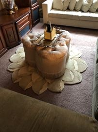 Cream colored stool and flower shaped rug