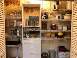Super enviously organized pantry. We got Crockpots, coffee makers, a collection of jars, water bottles -- is that a FONDUE SET?? IT IS!