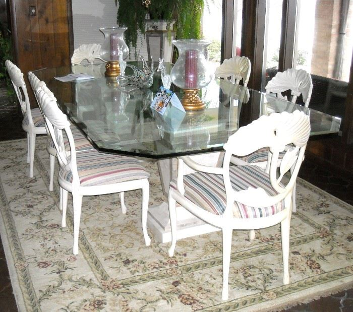 Large glass top dining table rests on two pedestals.  Eight  chairs.
