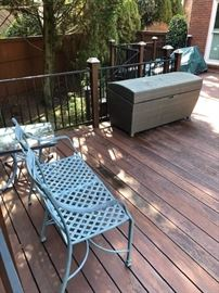 Iron patio bench and wicker outdoor storage chest.