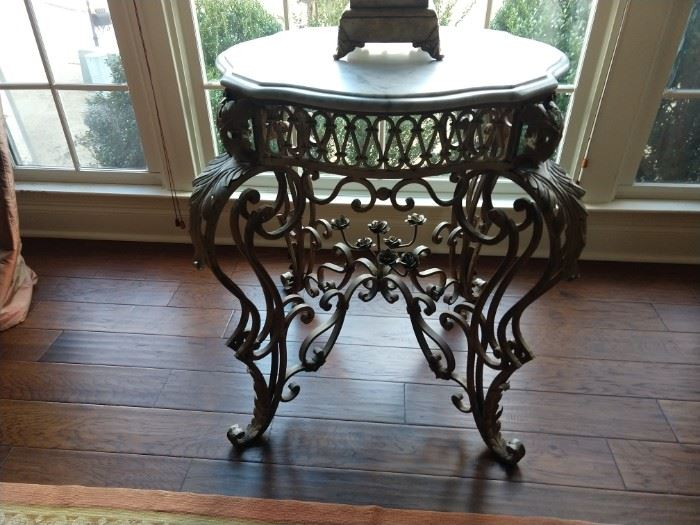 Love all the vintage wrought iron and marble side tables in this house!