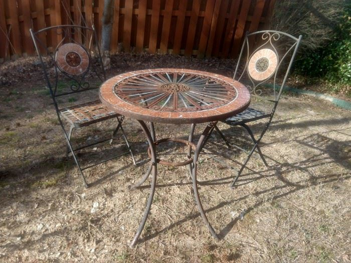 Nice little wrought iron table and two chairs for neighborhood gossip and tete a tete's.