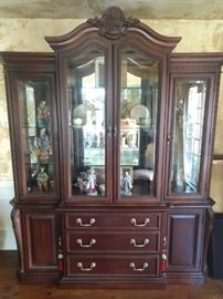 "Pristine Bernhardt ""La Scala"" collection lighted mahogany china cabinet, with beveled glass and mirrored back, measuring 94"" high at tallest point x 77"" wide x 22"" deep. The china cabinet has beveled glass doors, is lighted and has 3 glass shelves.  Base has 3 drawers and 2 doors with 1 shelf inside each; originally cost $4,850.00 in 2001."