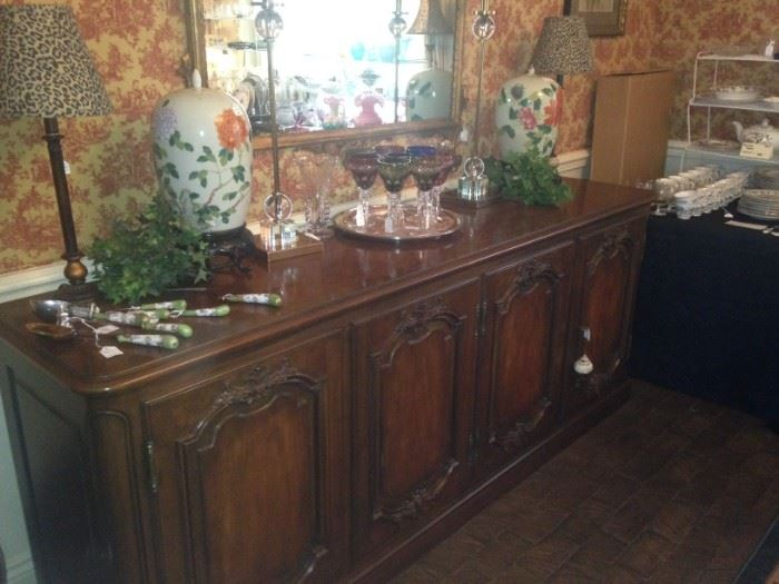 Extra long buffet provides serving and storage space; a gold framed mirror is above the buffet.