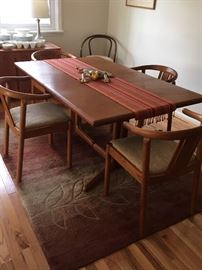 Set of Danish teak Dining Table (with one leaf) and 4 matching Chairs with upholstered seats. Lovely muted tones and leaf-pattern on 5' x 8' Rug.