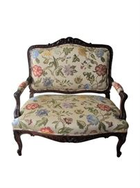 "Antique French carved settee beautifully upholstered in a hand woven silk floral vine motif. Fabric features a vibrant royal blue, cornflower blue, lilac, dark and light hues of rose with forest green and lighter green leaves on an ecru background. Double self welt grim throughout (including arms). Intricate carved detail on the crest and center apron resembling a pineapple symbol and acanthus leaf detail throughout including on cabriole legs. The back of the sofa has an exposed wood frame with a center splat which makes it eye-catching floated in a room as well as against a wall. The frame has been refurbished in a rich walnut stain and newly upholstered in a stunning floral fabric.                                                 Dimensions: 41""w x 23""d x 40.5""h • Seat=24""d x 17""h • Arm=24""h"