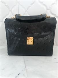 Lana Marks Medium Black Ostrich Handbag with gold clasp. (front)