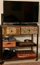Samsung 40 inch flatscreen HD, vintage Coca-Cola crates, antique cigar press, custom made TV cabinet With drawers space-on wheels.