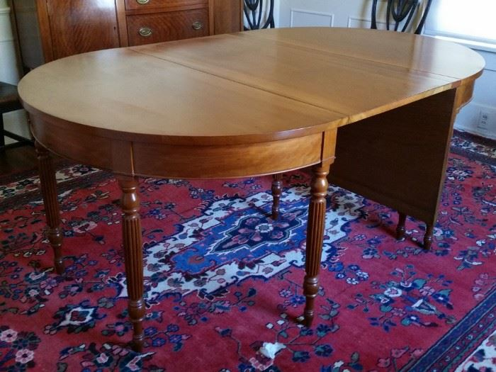 """The cherry table can be configured several different ways.  It can be 114"""" long with  removable leaf, 96"""" with both drop leaves up,  74"""" (shown here) with one drop leaf up, and 54"""" with both drop leaves down."""