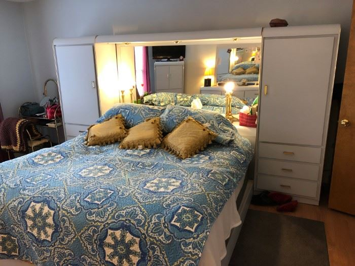 King Size Bed with mirror headboard, double side boards with shelves and draws. Light blue color.