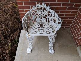Cast iron chair. house on the hill.