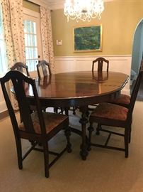 Antique dining room table with 6 chairs.  Includes 4 leaves and a padded table cover.